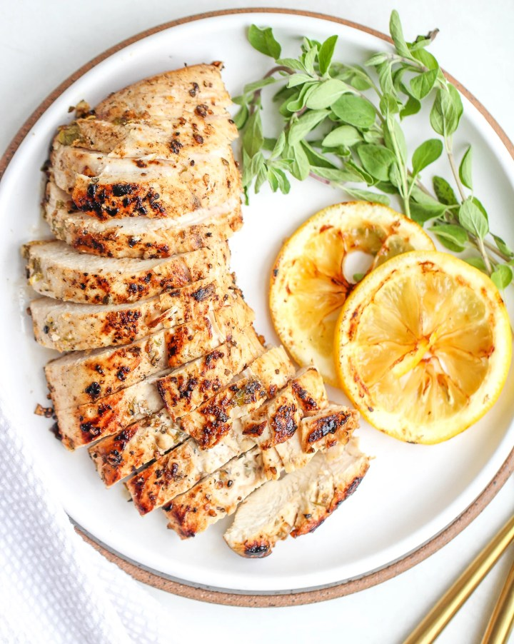sliced marinated greek chicken breast on a white plate with fresh oregano and sliced lemons