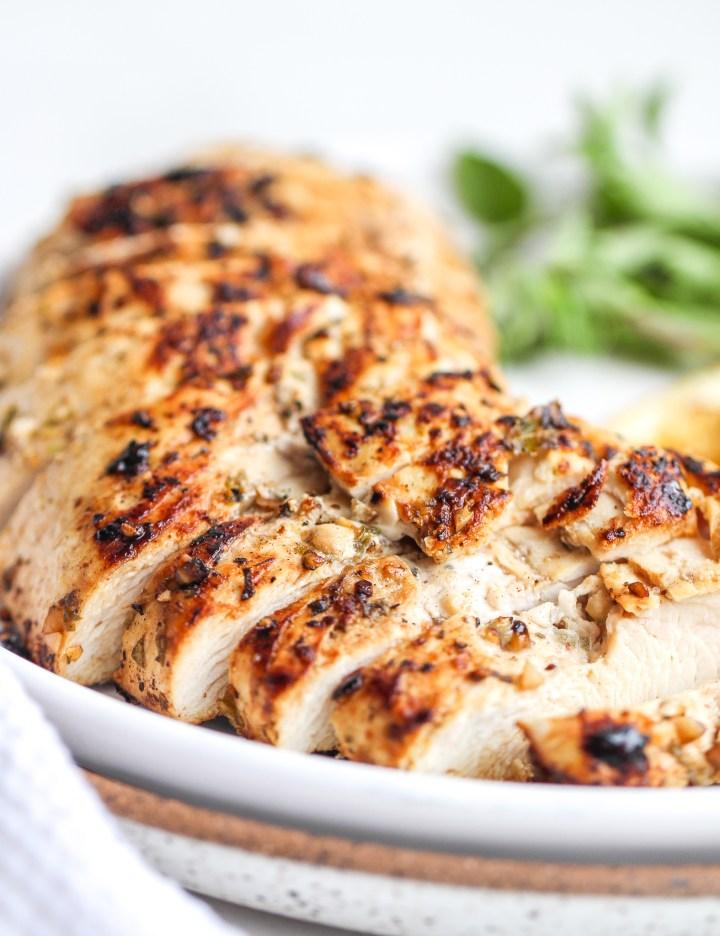 Marinated Greek chicken sliced on a ceramic plate
