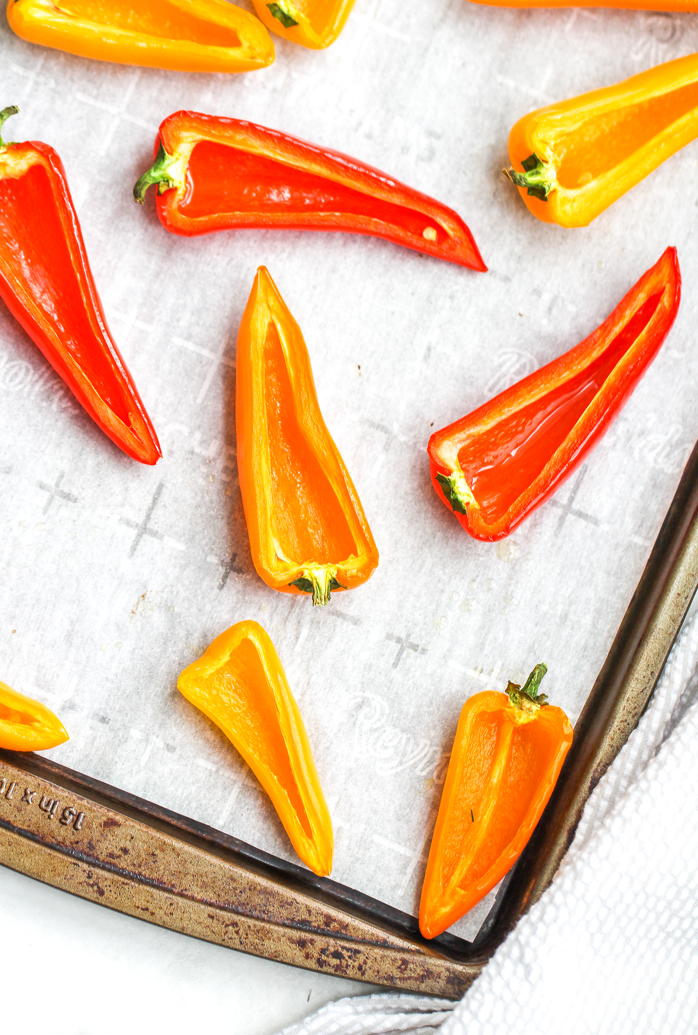 sliced sweet peppers on a parchment lined baking sheet