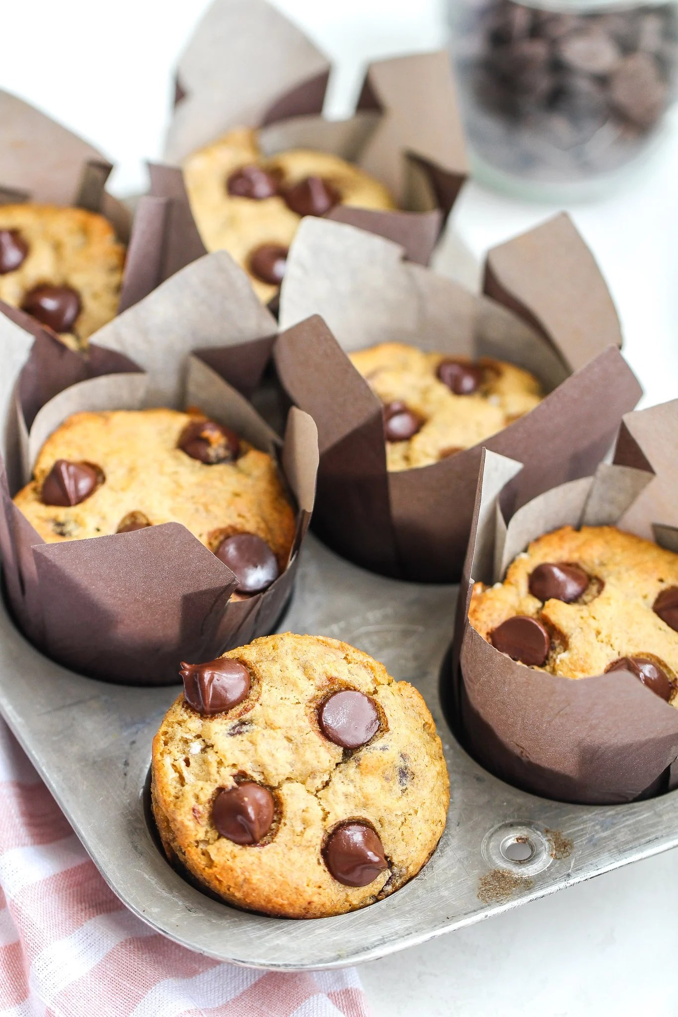 Chocolate chip banana muffins in a tin with brown liners and chocolate chips in the background