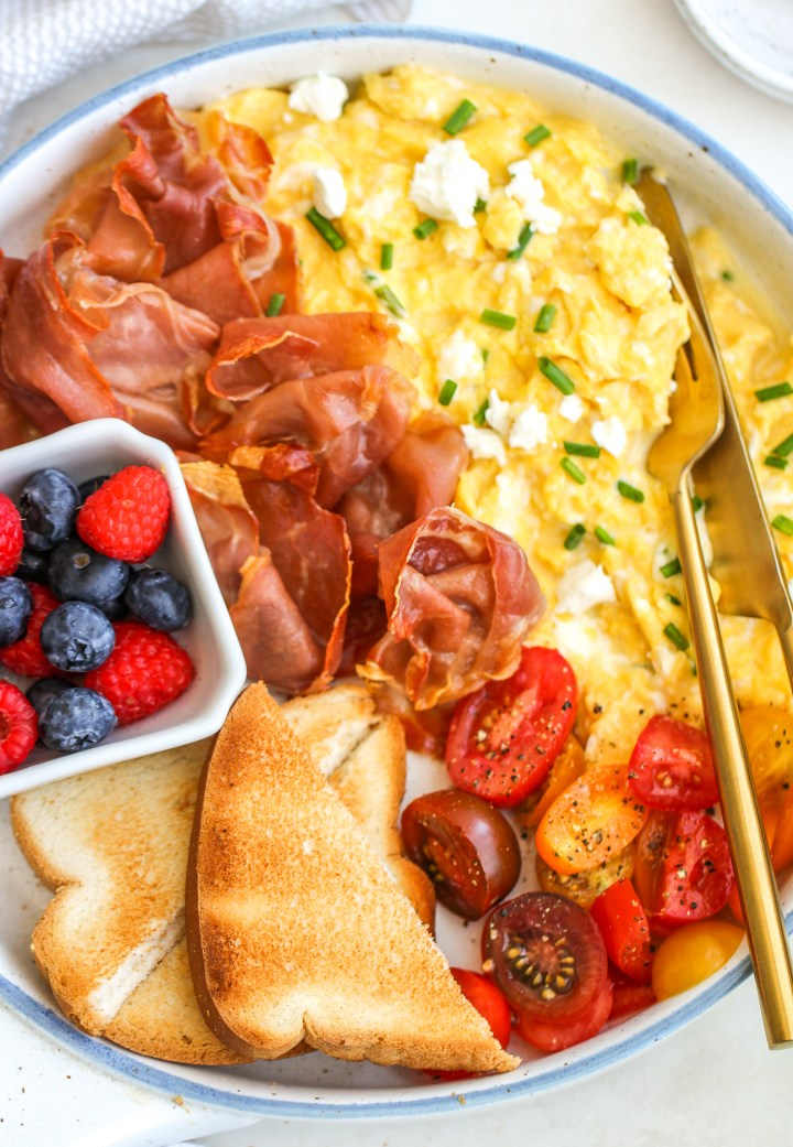 Creamy scrambled eggs on a serving platter topped with goat cheese and chives. Served alongside crispy prosciutto, a bowl of fresh berries, toast slices, and grape tomatoes sprinkled with fresh cracked pepper
