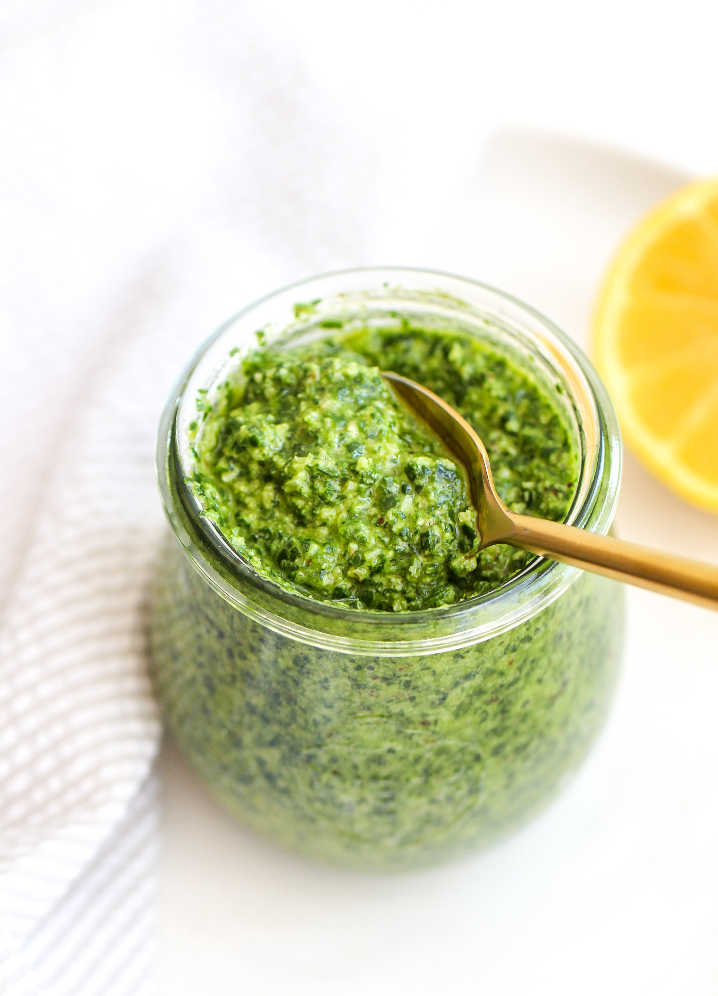 glass jar filled with spinach, Arugula and walnut pesto. there is a gold spoon in it and a lemon in the background