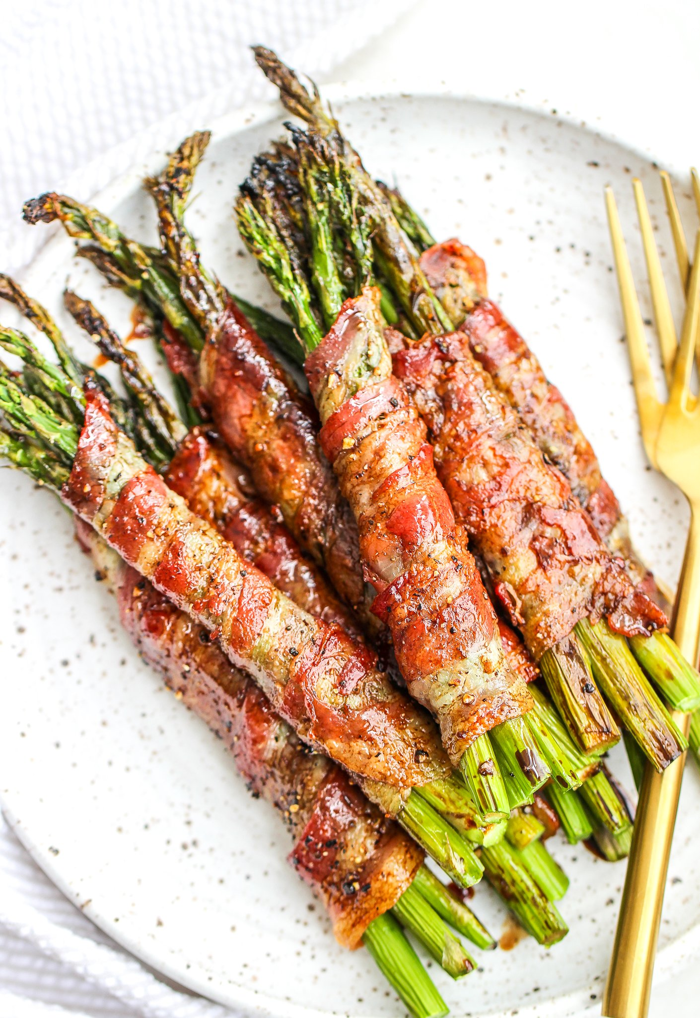 bacon wrapped asparagus bundles drizzled with balsamic reduction stacked on a ceramic plate with gold forks on the side of the plate