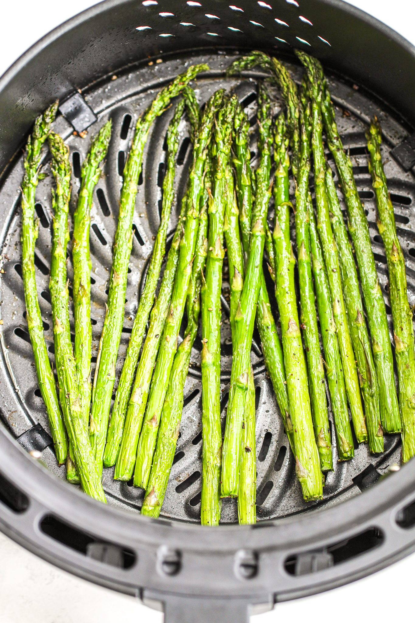 asparagus in an air fryer basket tossed with cooking spray and salt & pepper