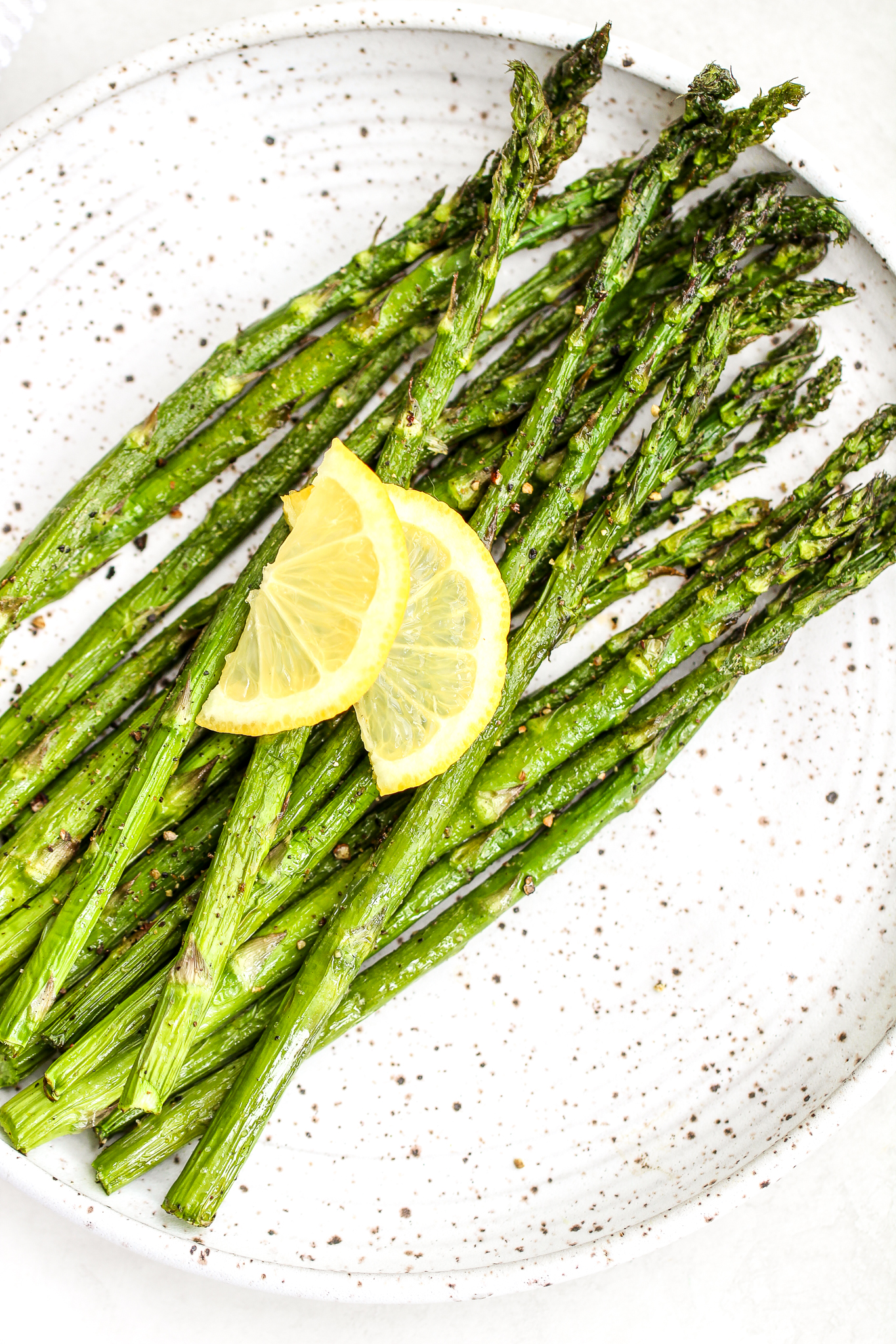 Air fryer asparagus on a ceramic plate topped with fresh cracked pepper and lemon slices