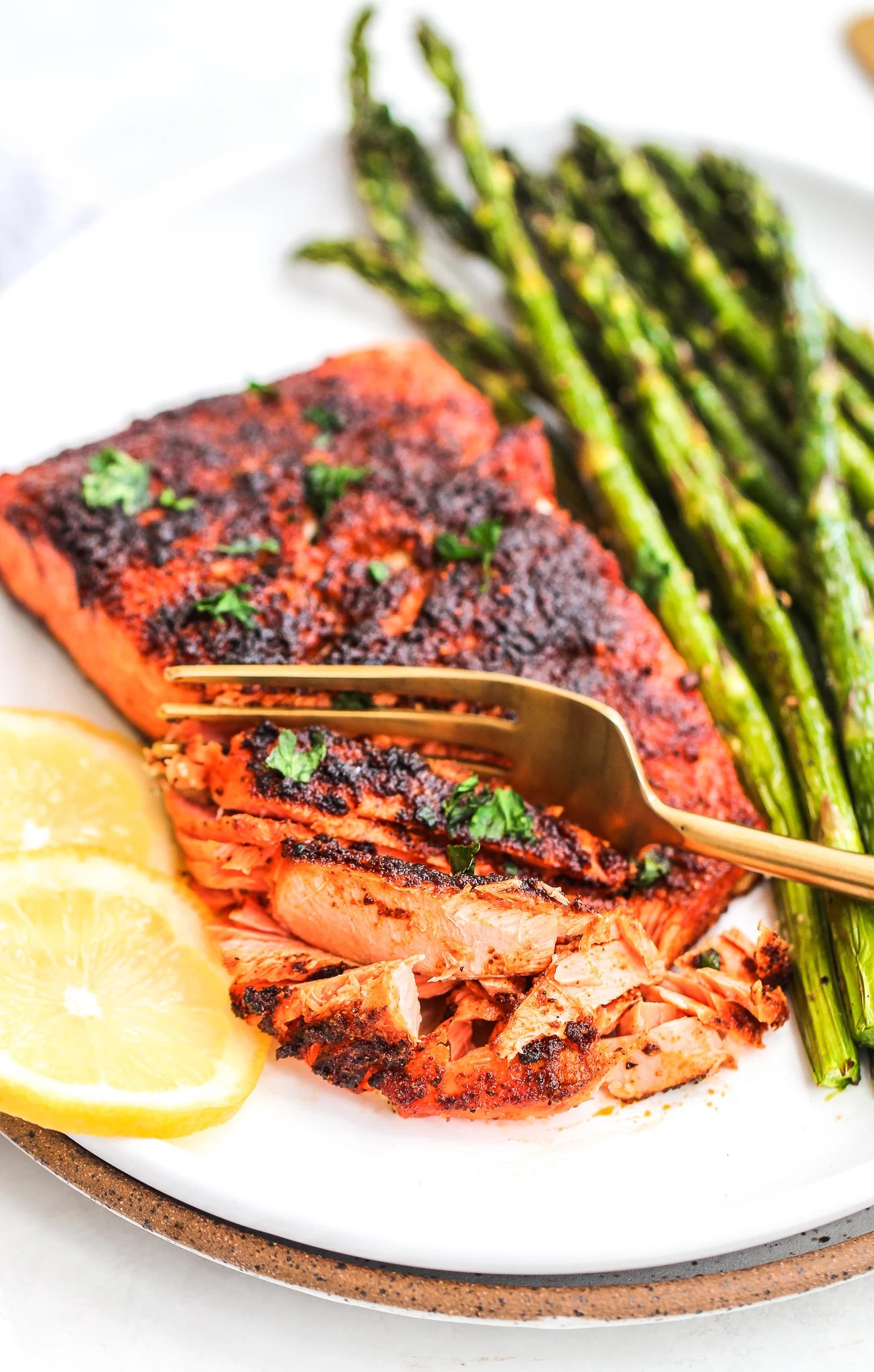 air fryer blackened salmon with a fork flaking it. There is cooked asparagus and fresh lemon on the side