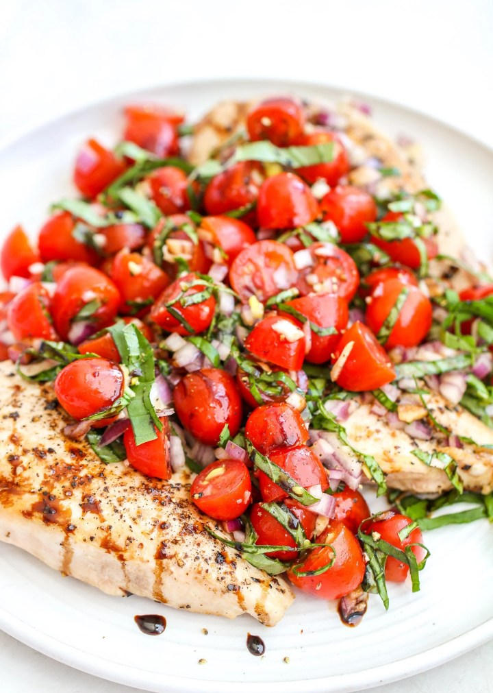 cooked chicken breasts on a platter covered with bruschetta topping - fresh tomatoes, red onion, garlic, basil and salt/pepper. It is drizzled with balsamic glaze