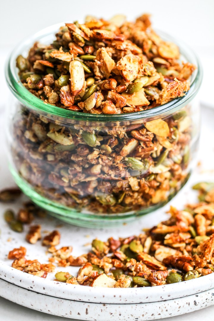 paleo granola in a glass storage jar, sitting on a speckled ceramic plate with some granola on the plate as well