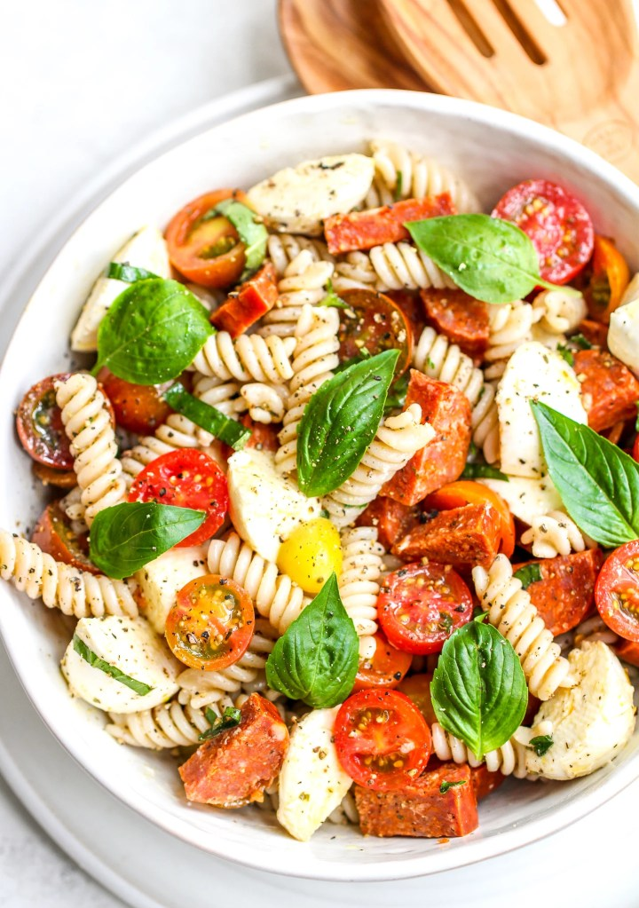 Italian pasta salad with spiral pasta, halved grape tomatoes, diced pepperoni and fresh basil leaves on the top. It is in a white serving bowl with wooden salad spoons on the side