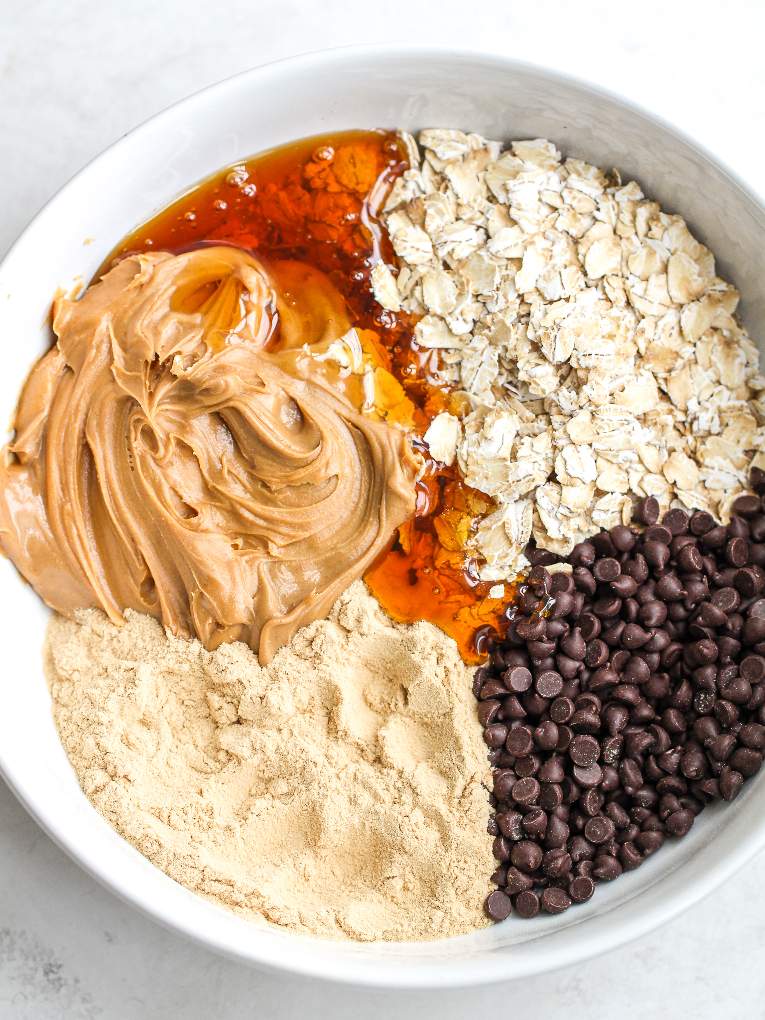 ingredients for peanut butter protein bites in a white bowl  oats, vanilla protein powder, creamy peanut butter, chocolate chips and honey
