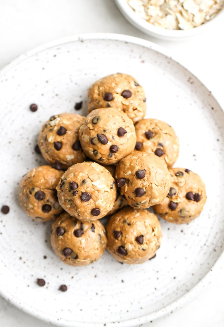 overhead photo of peanut butter protein bites - bites are rolled into balls with chocolate chips  they are sitting on a speckled ceramic  plate