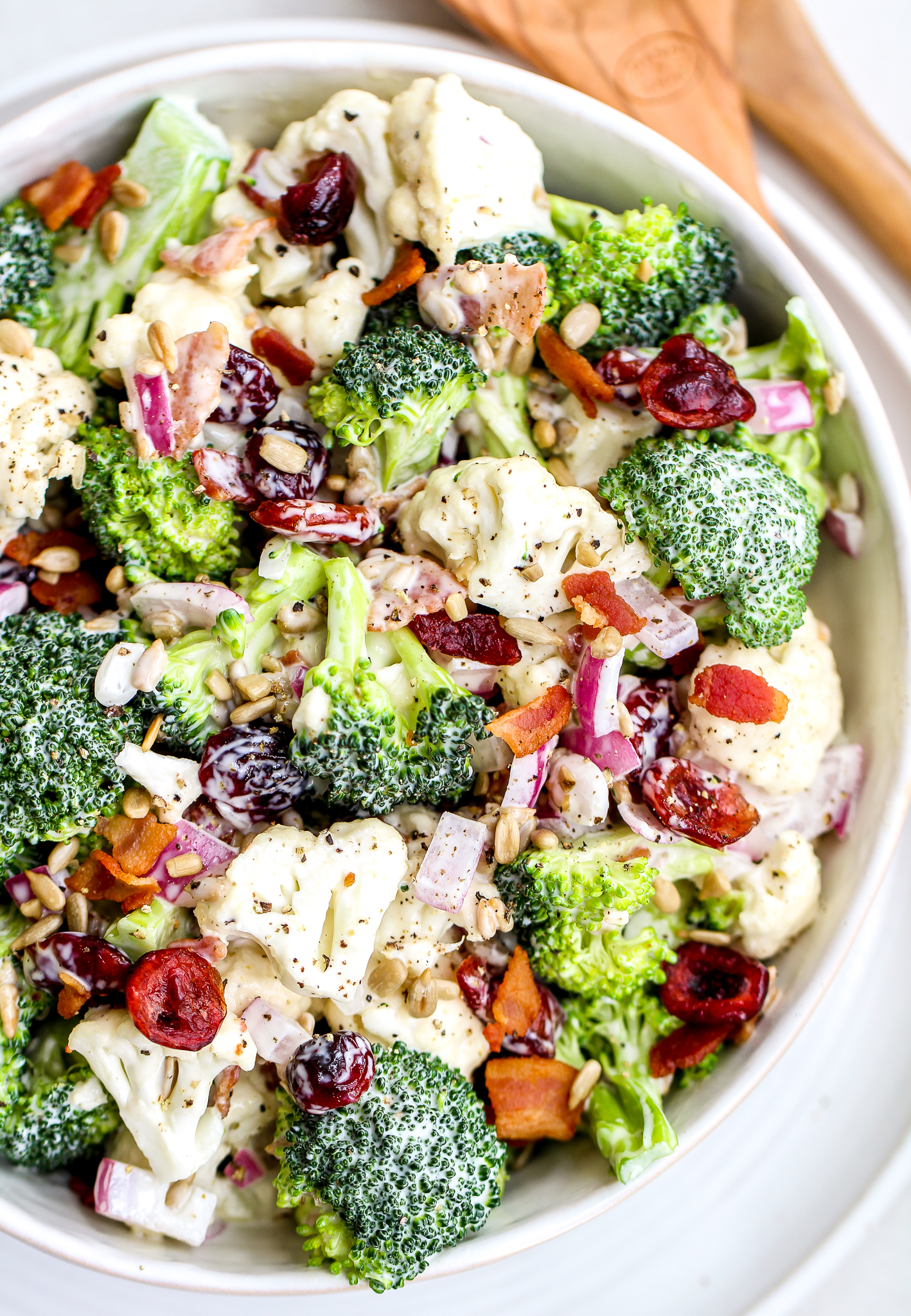 easy broccoli cauliflower salad in a white serving bowl with wooden salad spoons in the background. You can see the broccoli and cauliflower florets in a creamy dressing with sunflower seeds, chopped red onion, chopped bacon and dried cranberries. There is fresh cracked pepper on the top