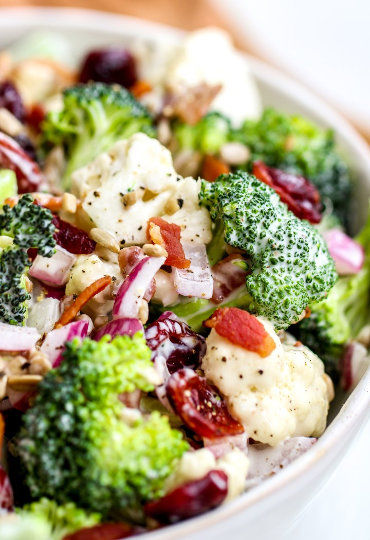 close up photo of broccoli cauliflower salad in a white serving dish