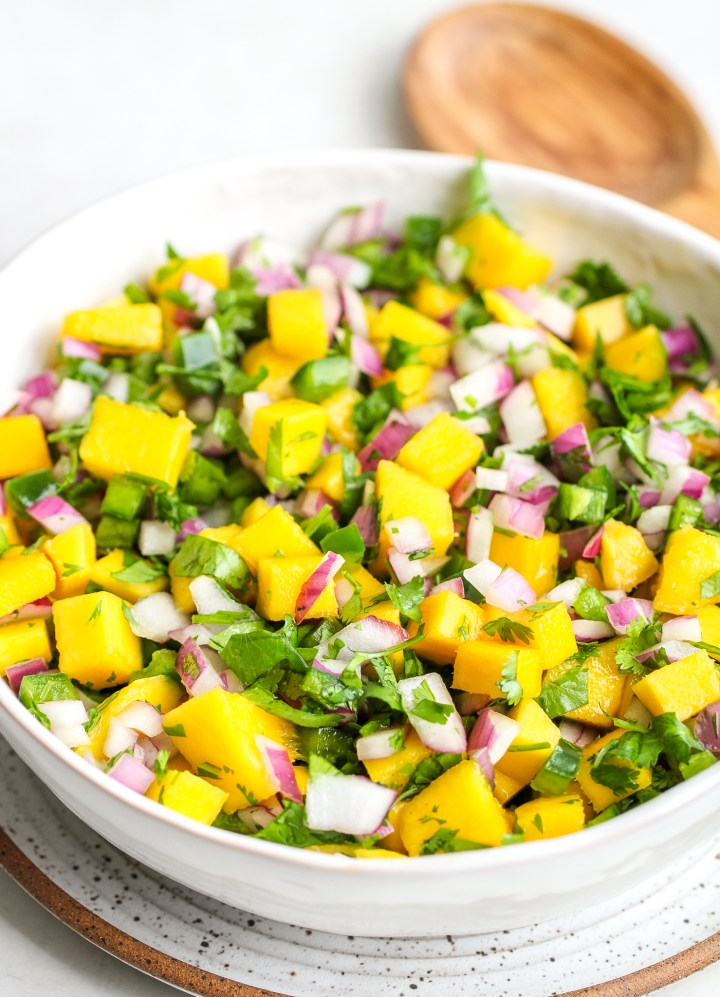 side photo of fresh mango salsa in a white serving bowl - there is bright yellow cubed mango, diced green jalapeño, chopped cilantro and diced red onion