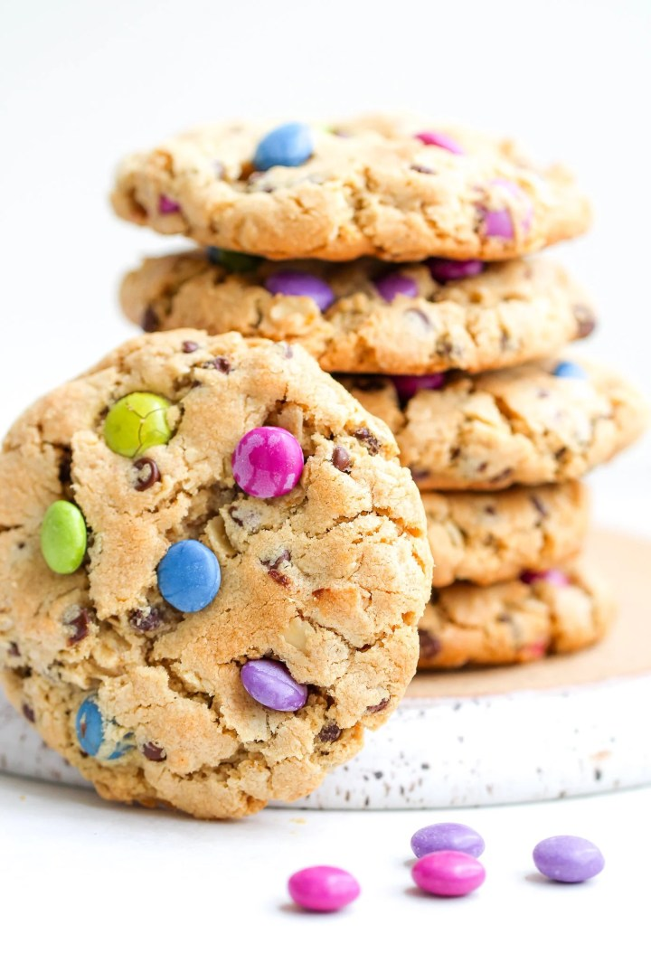 stack of gluten free monster cookies with candy coated chocolates sprinkled in front