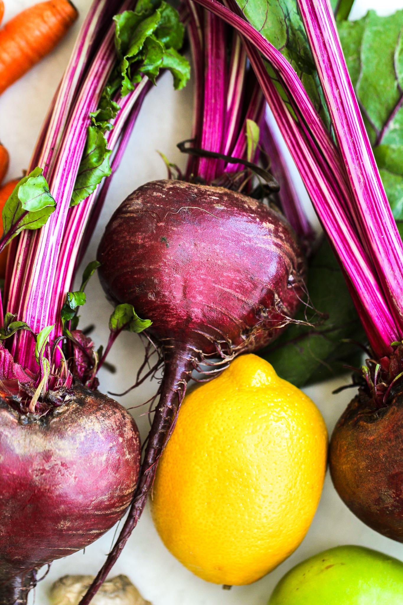 beautiful flat lay of fresh produce, lovely purple beets, bright yellow lemon, green apple and fresh carrots