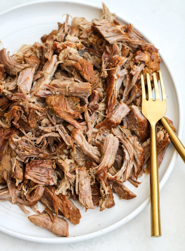 instant pot pulled pork on a white serving plate with two gold forks