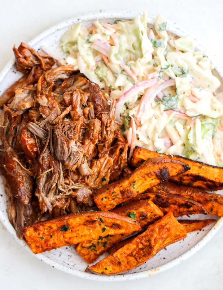 instant pot pulled pork on a white serving plate with a side of coleslaw and sweet potato wedges
