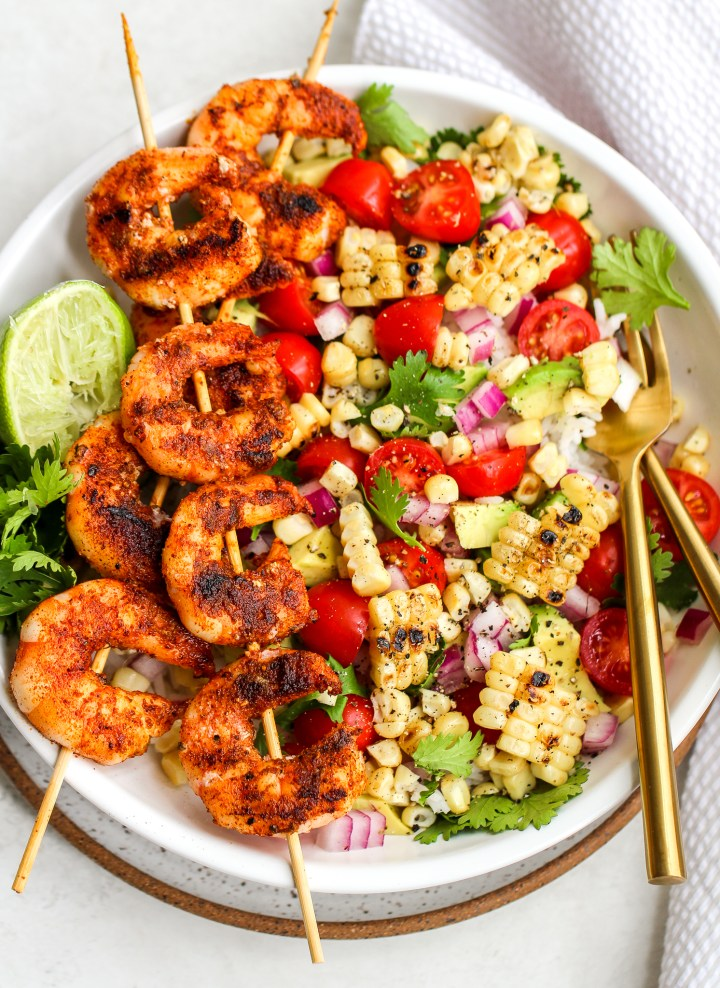 spiced grilled shrimp on skewers over a bowl of rice and fresh salsa ingredients