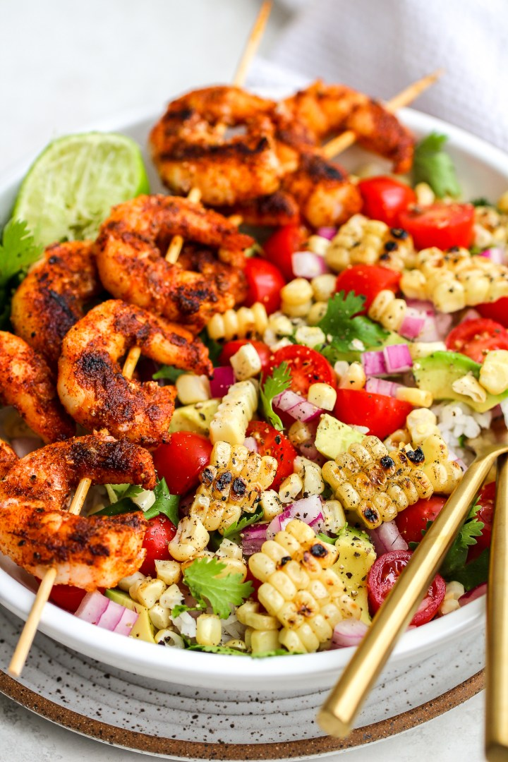 spiced grilled shrimp on wooden skewers laid over a bowl of fresh grilled corn and a variety of fresh veggies - diced red onion, cilantro leaves, grape tomatoes, avocado and lime