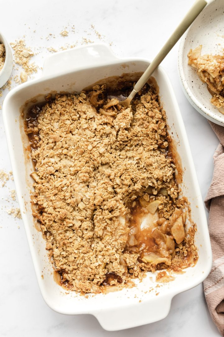 gluten free apple and pear crisp in a 9x13 white baking dish - it has a scoop out of it and a spoon resting in it