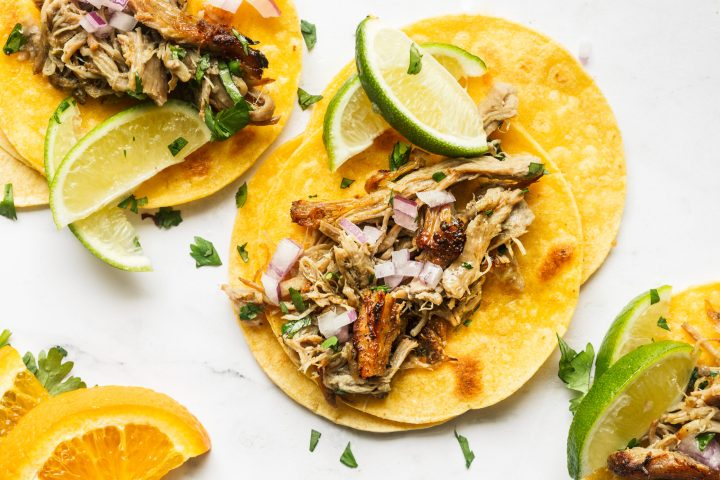 pork carnitas in corn tortillas topped with onion and served with lime wedges