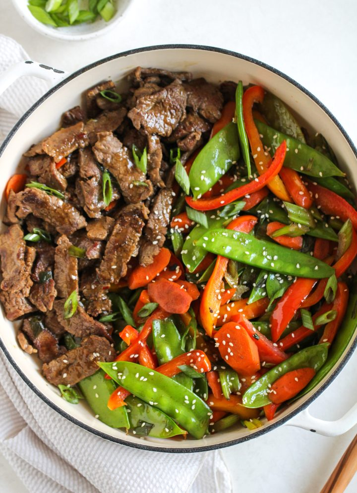 beef and veggie stir fry in a large white skillet - topped with white sesame seeds and fresh green onions cut on the diagonal