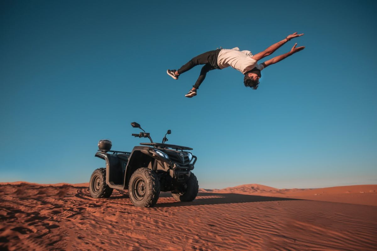 man backflipping on gray sand