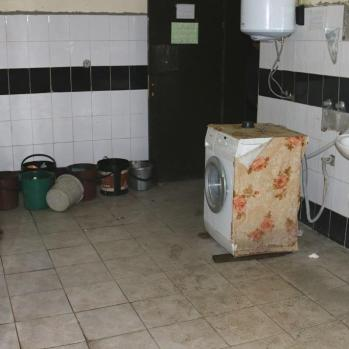 The communal washroom, where several taps are on and overflowing onto the floor.