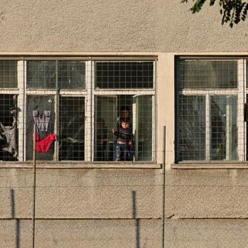 A little boy stands in the window of the camp staring out through the wire mesh.