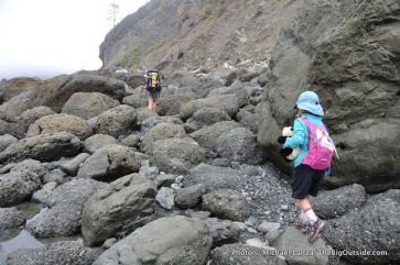 Alex hiking a boulder-strewn section of beach.