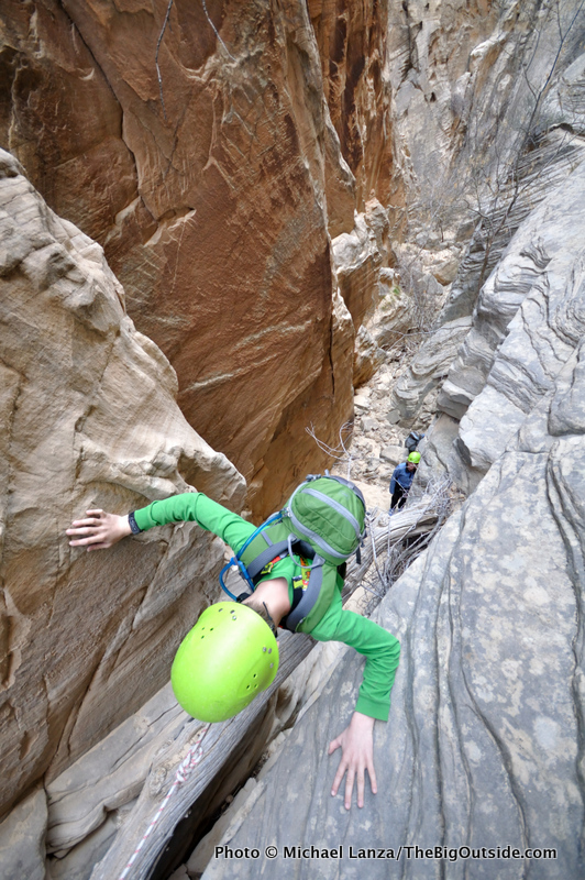 A young boy getting lowered on a rope in a slot canyon in Capitol Reef National Park.
