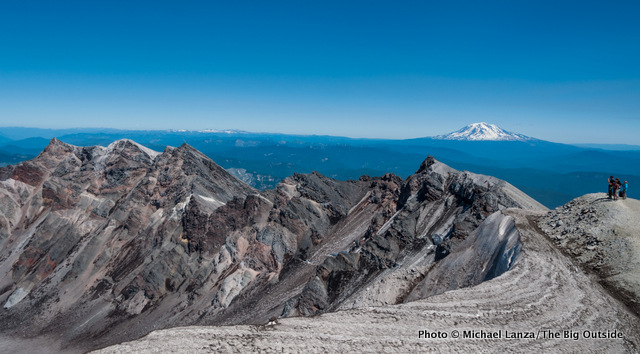 The crater rim of Mount St. Helens with Mount Adams in the distance.