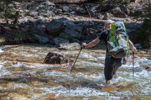 A backpacker fording Pettit Lake Creek, Sawtooth Mountains, Idaho.