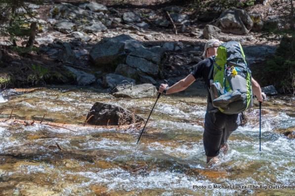 A backpacker fording Pettit Lake Creek, Sawtooth Mountains, Idaho.