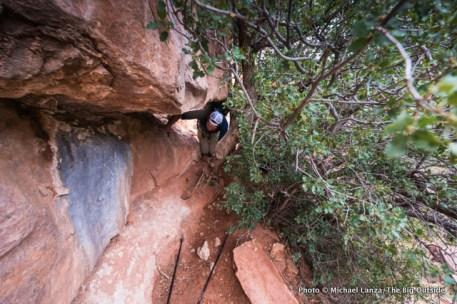 Jon Dorn crawling through a tight spot above Royal Arch Canyon.