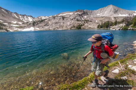 A young boy backpacking by Cove Lake in the Big Boulder Lakes, White Cloud Mountains, Idaho.
