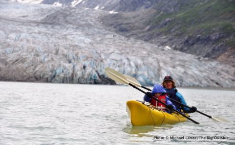 A mother and young boy sea kayaking below Reid Glacier in Alaska's Glacier Bay National Park.