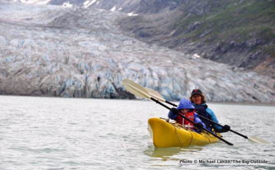 A mother and young boy sea kayaking below Reid Glacier in Alaska's Glacier Bay National Park.