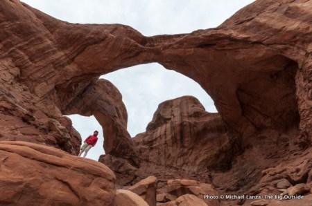 Teenage boy beneath Double Arch, Arches National Park.