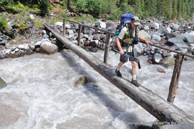 A backpacker crossing Winthrop Creek on the Wonderland Trail in Mount Rainier National Park.