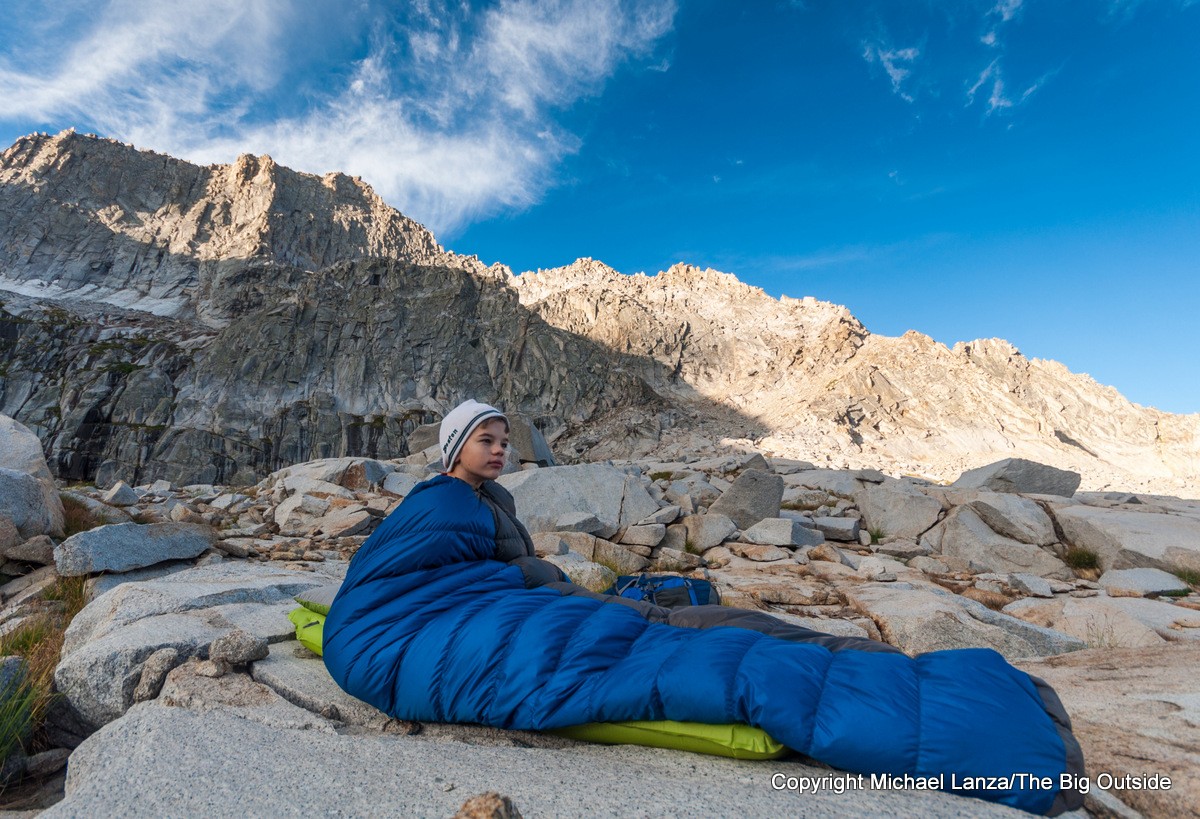 A young boy in a sleeping bag while backpacking in Sequoia National Park.