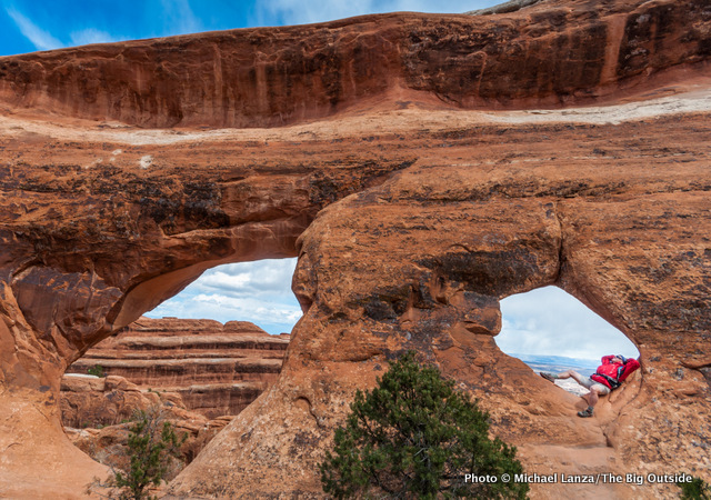 A hiker in Partition Arch, in Devils Garden, Arches National Park.