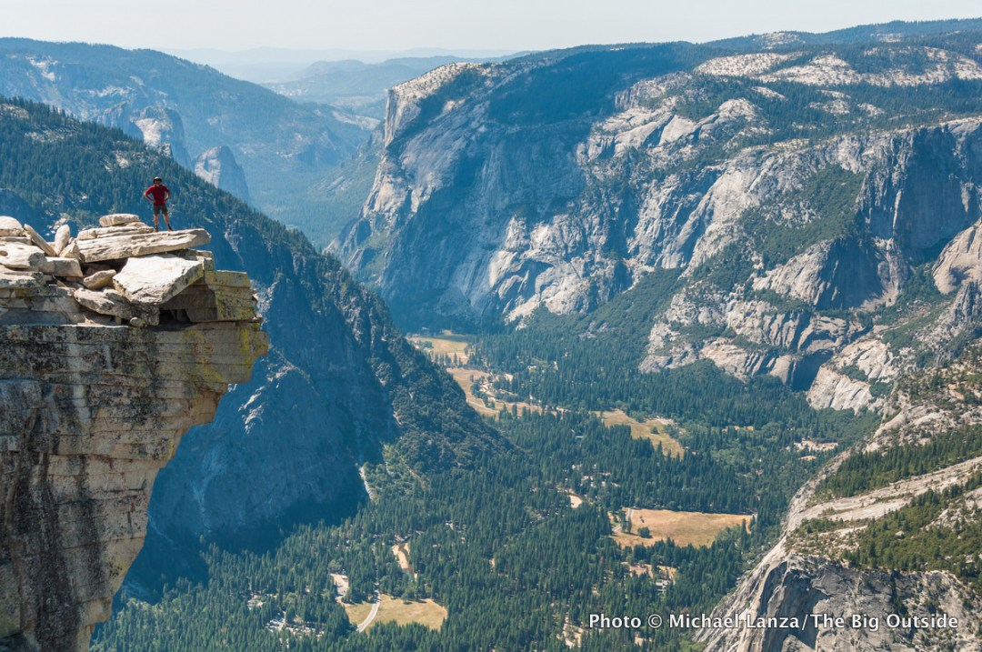 A hiker high above Yosemite Valley on Half Dome, Yosemite National Park.