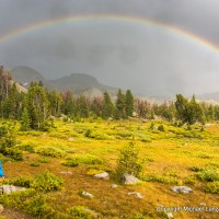 A backpacker and a rainbow in Wyoming's Wind River Range.