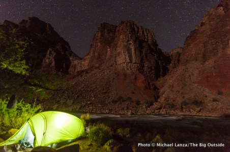 A campsite at night by the Colorado River at Hance Rapids in the Grand Canyon.