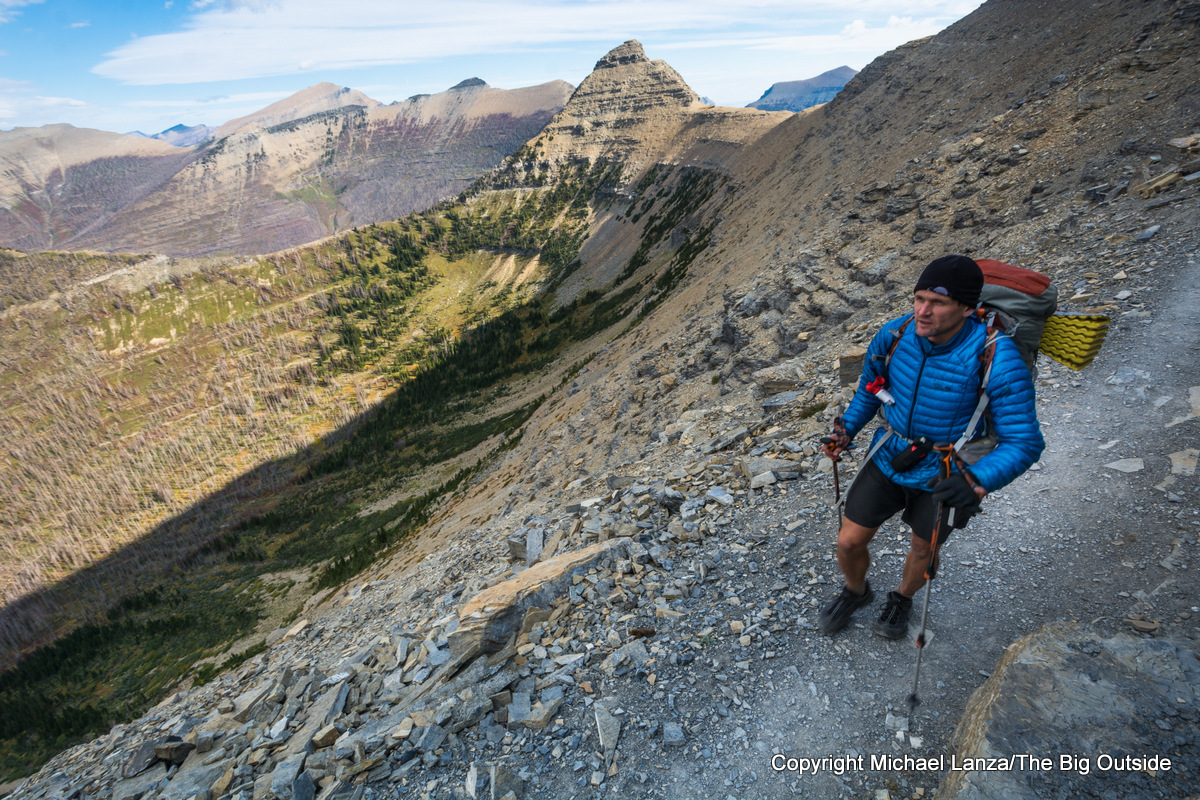 A backpacker in cold wind on the Dawson Pass Trail in Glacier National Park.
