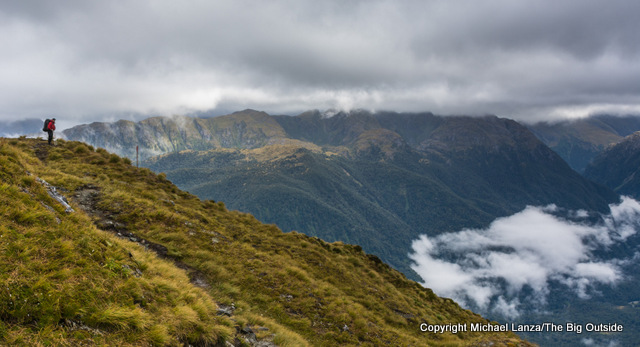 A trekker hiking the Dusky Track in the Pleasant Range in New Zealand's Fiordland National Park.