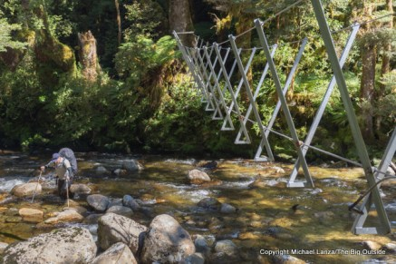 A trekker fording a river below a walkwire on the Dusky Track, Seaforth River Valley, Fiordland National Park, New Zealand.