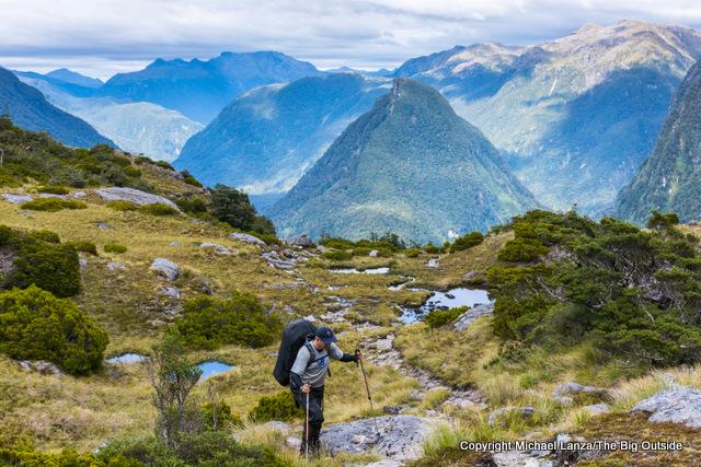 A trekker climbing to Centre Pass on the Dusky Track, Fiordland National Park, New Zealand.